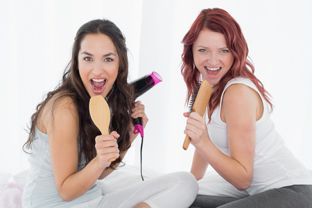 Portrait of two cheerful young female friends singing into hairbrushes on bed at home photo