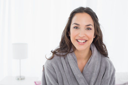 Portrait of a happy young female in bathrobe sitting on bed at home photo