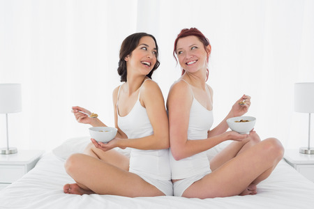 Side view of two smiling young female friends with bowls sitting on bed at home photo