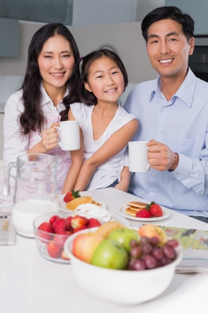 Portrait of a happy young girl enjoying breakfast with parents at table in the house photo