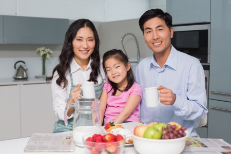 Portrait of a happy young girl enjoying breakfast with parents at table in the kitchen photo