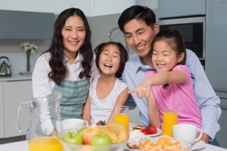 Portrait of a cheerful family of four enjoying healthy breakfast in the kitchen at home photo