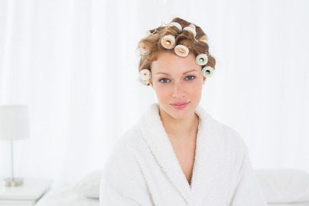 Portrait of a beautiful young woman in bathrobe and hair curlers sitting on bed at home photo