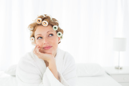 Thoughtful young woman in bathrobe and hair curlers sitting on bed at home photo