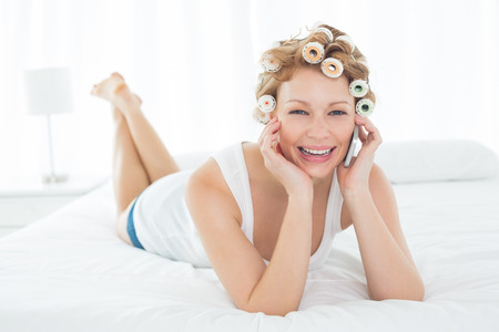 Portrait of a beautiful young woman in hair curlers using cellphone while lying in bed at home photo