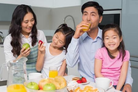sappen: Vrolijke gezin van vier genieten van gezond ontbijt in de keuken thuis Stockfoto