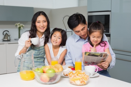 Portrait of a happy family of four enjoying healthy breakfast in the kitchen at home photo