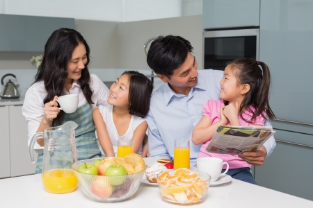 Happy family of four enjoying healthy breakfast in the kitchen at home