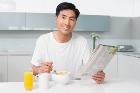 Portrait of a smiling young man having cereals while reading newspaper in the kitchen at home photo