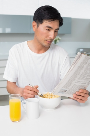 Serious young man having cereals while reading newspaper in the kitchen at home photo