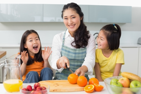 Portrait of a smiling woman with cheerful two daughters cutting fruit in the kitchen at home photo
