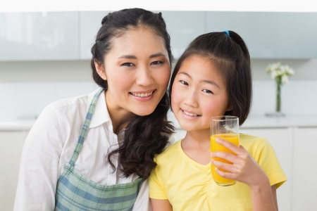 Portrait of a young girl holding orange juice with her mother in the kitchen at home photo