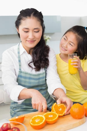 Woman with her young daughter cutting fruit in the kitchen at home photo