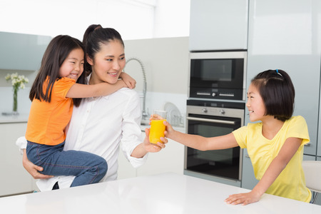 Girl offering her mother a glass of orange juice in the kitchen at home