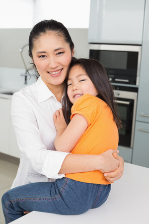 Portrait of a mother carrying her young daughter in the kitchen at home photo