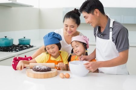 Happy family of four preparing cookies in the kitchen at home Foto de archivo