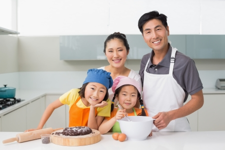 Portrait of a family of four preparing cookies in the kitchen at home photo