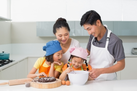 Happy family of four preparing cookies in the kitchen at home Standard-Bild