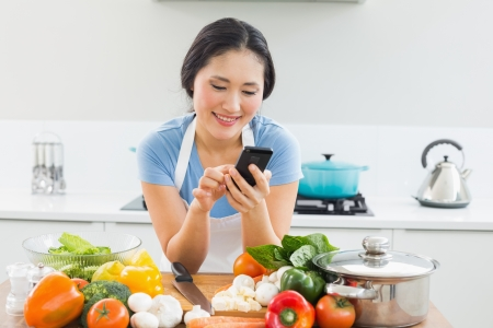 Smiling young woman text messaging in front of vegetables in the kitchen at home