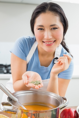 garnishing: Close-up of a smiling woman garnishing refreshing smoothie or puree