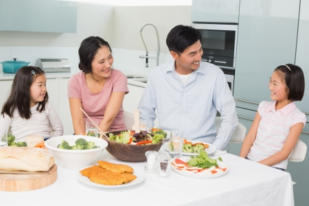 Cheerful family of four enjoying healthy meal in the kitchen at home photo