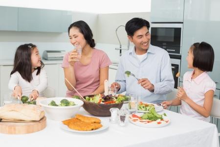 comer sano: Familia de cuatro j�venes disfrutar de comida saludable en la cocina en el hogar