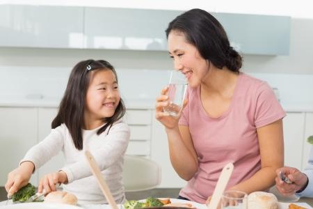 小さな女の子と、母が自宅の台所で食べ物を食べる 写真素材 - 25479690