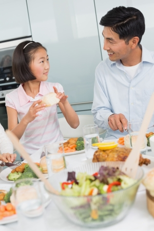 Father watching little girl eat food in the kitchen at home photo