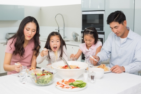 Happy family of four enjoying spaghetti lunch in the kitchen at home photo