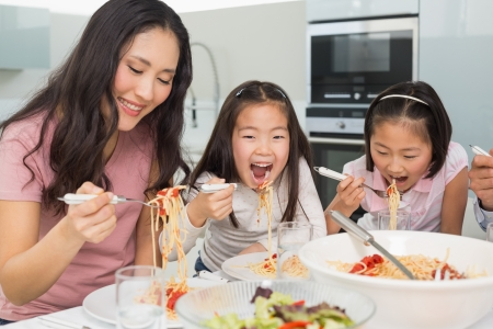 Woman with her two happy kids enjoying spaghetti lunch in the kitchen at home photo