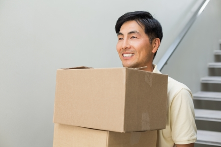 relocating: Smiling young man carrying boxes against staircase