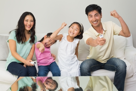 Portrait of a happy family of four watching tv in the living room at home 写真素材