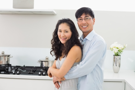 Portrait of a young man embracing woman from behind in the kitchen at home photo