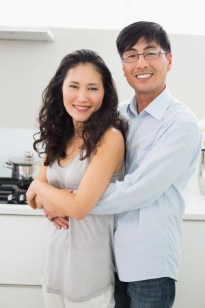 mujer de espaldas: Retrato de un joven abrazando a la mujer por detr�s en la cocina en el hogar