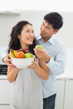 Young man and woman holding bowl full of fruit in the kitchen at home photo