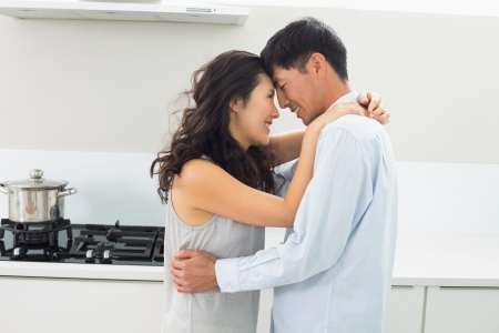 Side view of a young man embracing woman in the kitchen at home