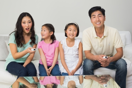 Portrait of a happy family of four watching tv in the living room at home photo