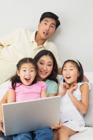 Portrait of a happy shocked family of four using laptop at home photo