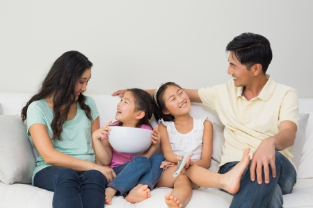 Happy family of with remote control and bowl sitting on sofa in the living room at home Stock Photo - 25480819