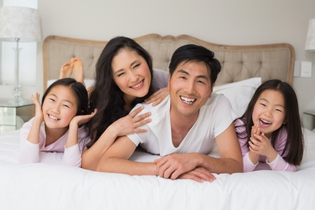 Portrait of a cheerful family of four lying in bed at home photo