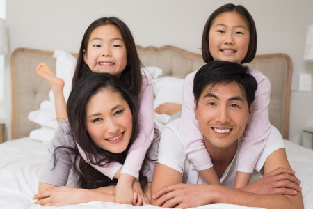 Portrait of a loving family of four lying in bed at home photo