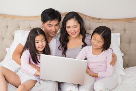 Happy relaxed family of four using laptop in bed at home photo