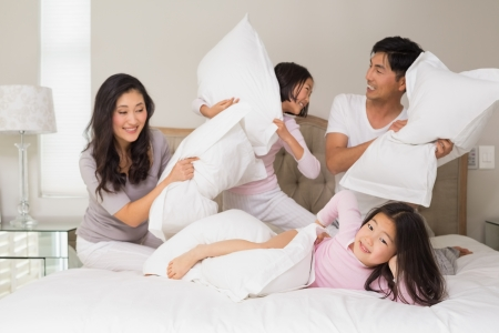 pillow fight: Cheerful kids and parents  having pillow fight on bed at home