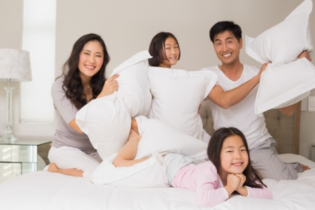 Cheerful kids and parents  having pillow fight on bed at home photo