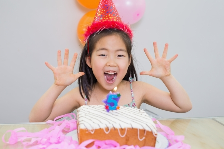 Close-up portrait of a cheerful little girl at her birthday party