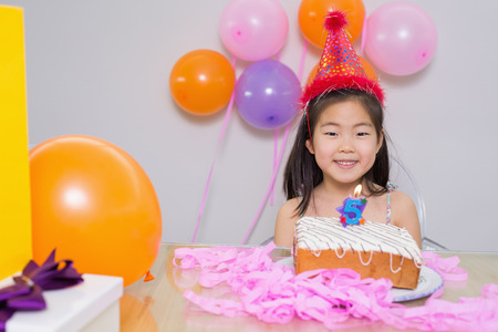 Close-up portrait of a cheerful little girl at her birthday party photo