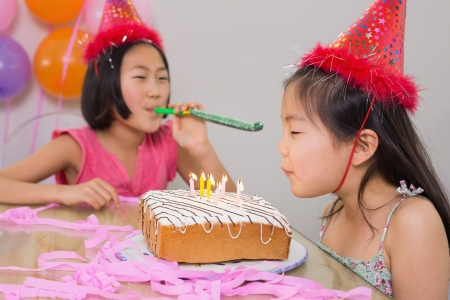 noisemaker: Girl blowing noisemaker while her sister blow the birthday candles at a party