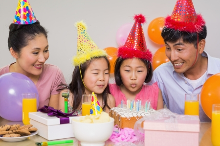 Cheerful family of four with cake and gifts at a birthday party photo