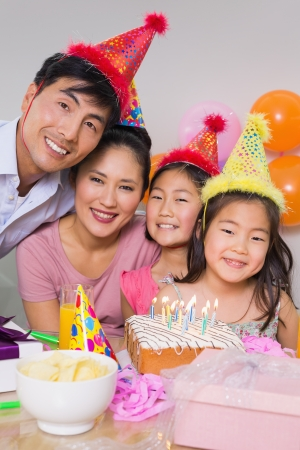 Portrait of a family of four with cake and gifts at a birthday party photo