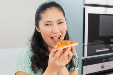 Close-up portrait of a smiling young woman eating a slice of pizza in the kitchen at home photo